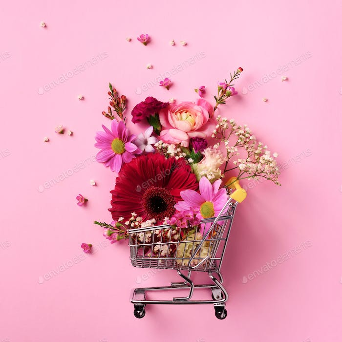 Shopping trolley with flowers on pink punchy pastel background. Banner with copy space. Top view