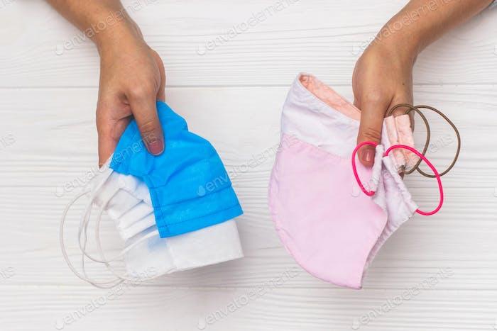 Hände halten wiederverwendbare Gesichtsmasken und medizinische Einmalmasken