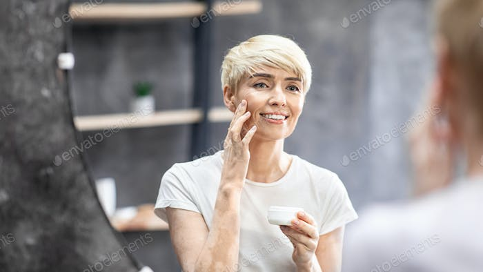 Middle-Aged Woman Applying Facial Cream Standing In Bathroom