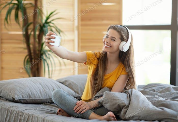 Glückliches junges Mädchen in Kopfhörern nehmen Selfie mit mobilen Gerät auf dem Bett zu Hause