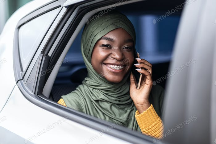 Black muslim woman traveling on car back seat and talking on cellphone