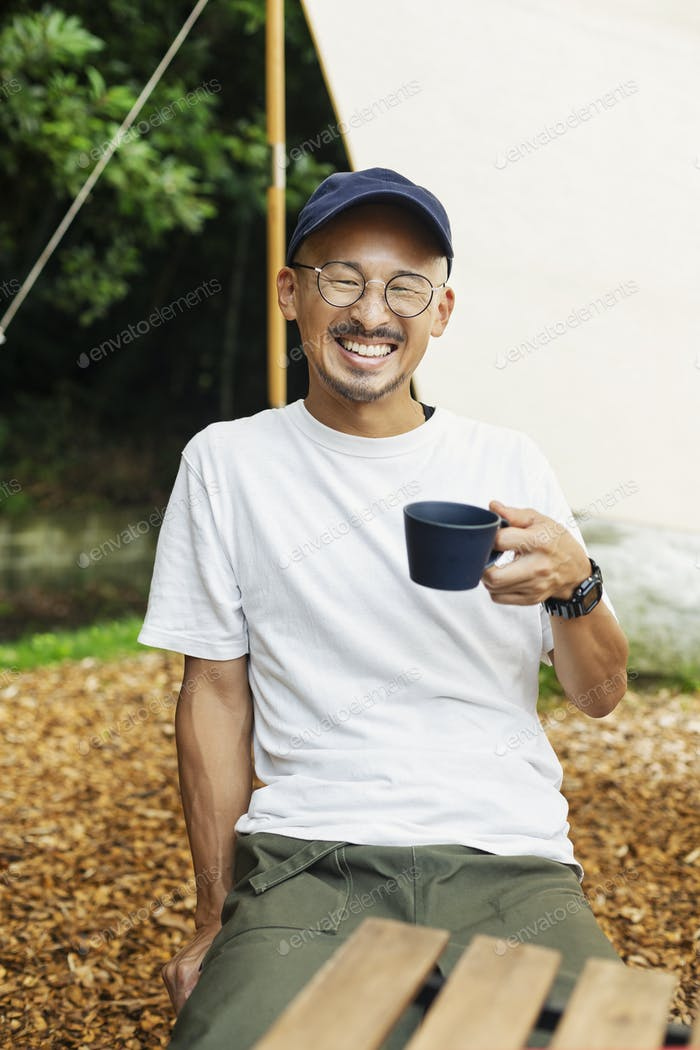 Smiling Japanese man wearing baseball cap and glasses sitting outdoors at a table, drinking cup of