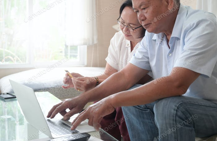 Old couples practice using laptops for online shopping and payments.