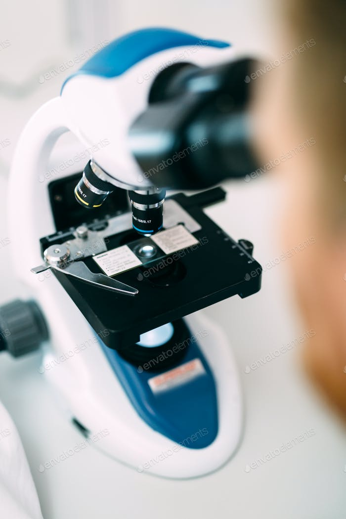 Closeup picture of researcher looking through microscope