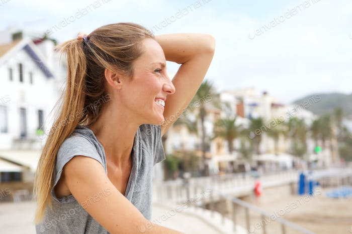 happy young woman smiling outside by the beach