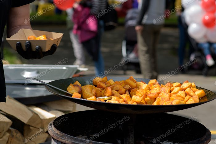 Chunks of fried potatoes in a large skillet during the street food festival.
