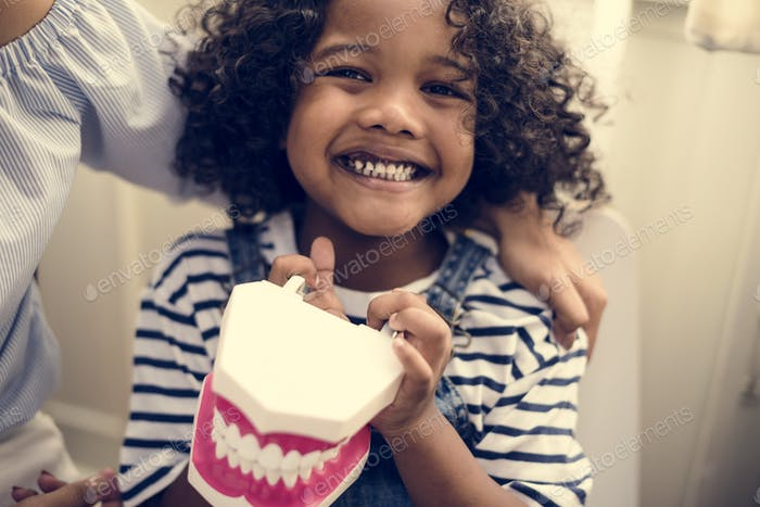 Cheerful young kid holding a dental model