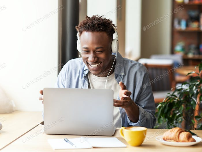 Online communication. Cheerful African American man in headset talking to friends on laptop at city