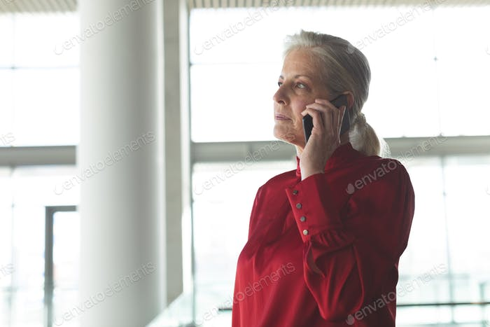 Side view of senior Caucasian businesswoman talking on mobile phone in modern office building