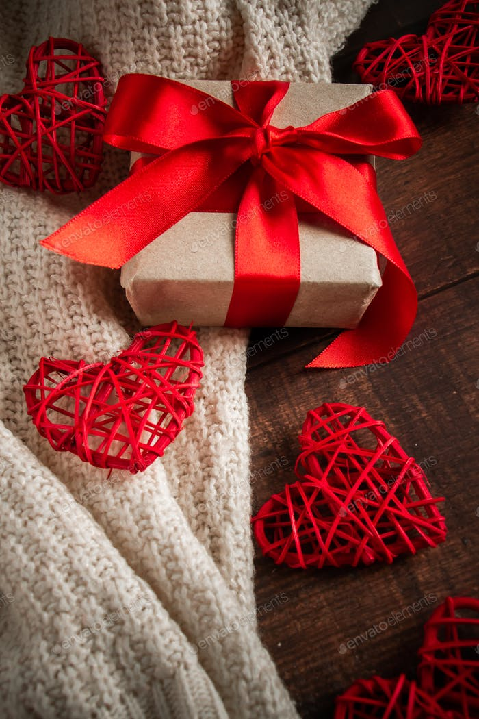 Gift box with red ribbon and hearts.