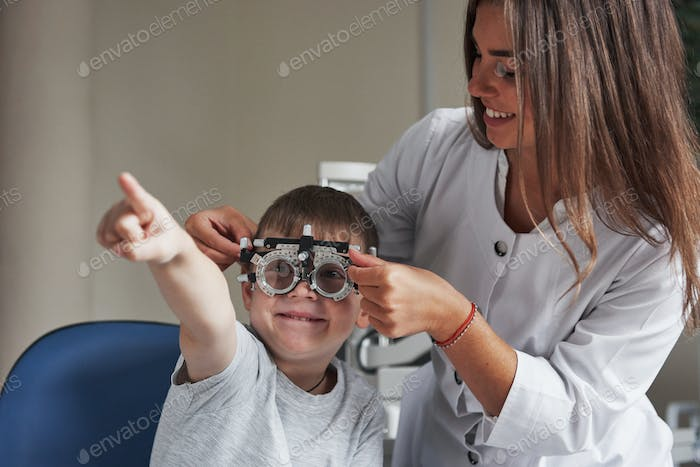 Smiling and reading. Child sitting in the doctor's cabinet and have tested his visual acuity