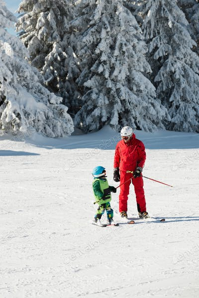 Ski trainer and little boy skiing