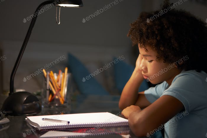 Unhappy Young Boy Studying At Desk In Bedroom In Evening