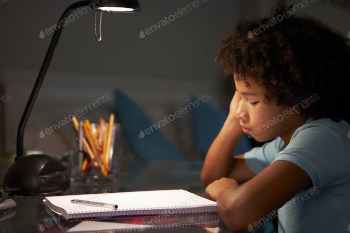 unglücklich junge junge studieren bei Schreibtisch in Schlafzimmer in Abend