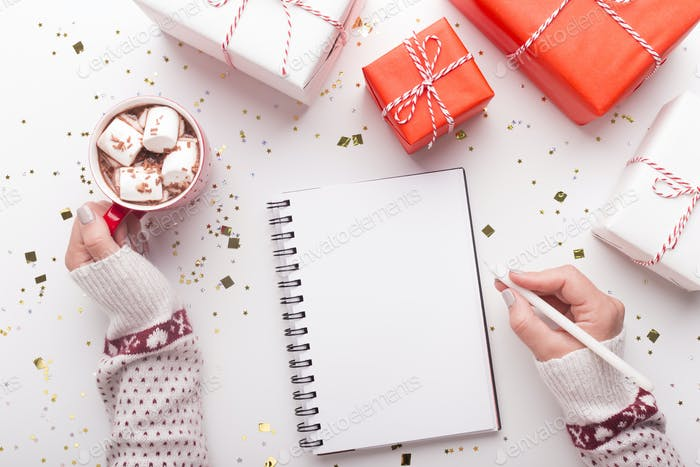 Woman with notepad, cacao and Christmas presents