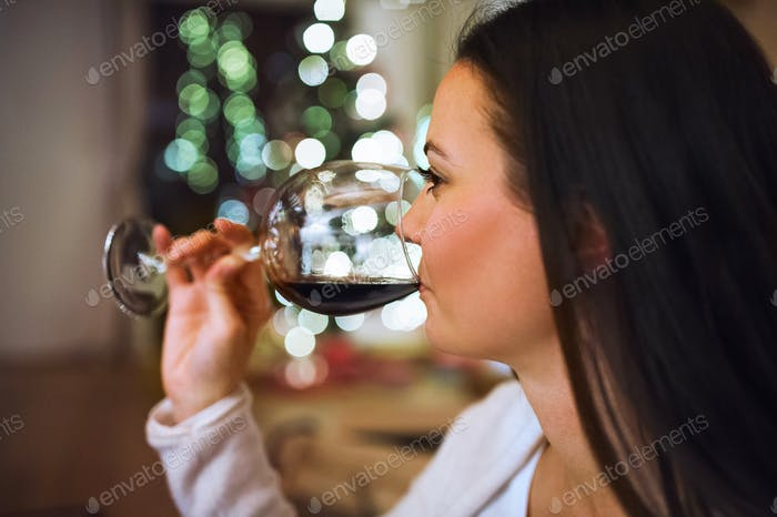 Young woman drinking wine at Christmas time.