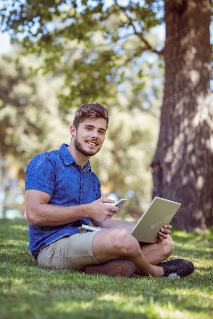 Hipster using laptop and phone in the park on a summers day