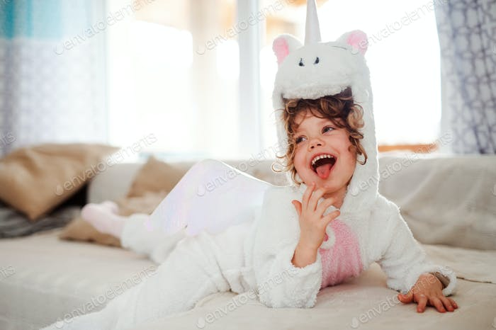 A portrait of small girl in unicorn mask lying on sofa at home.