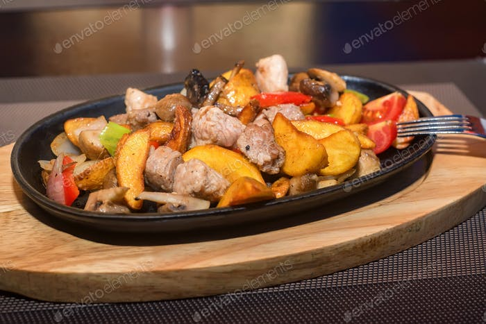 Roasted meat and vegetables on frying pan