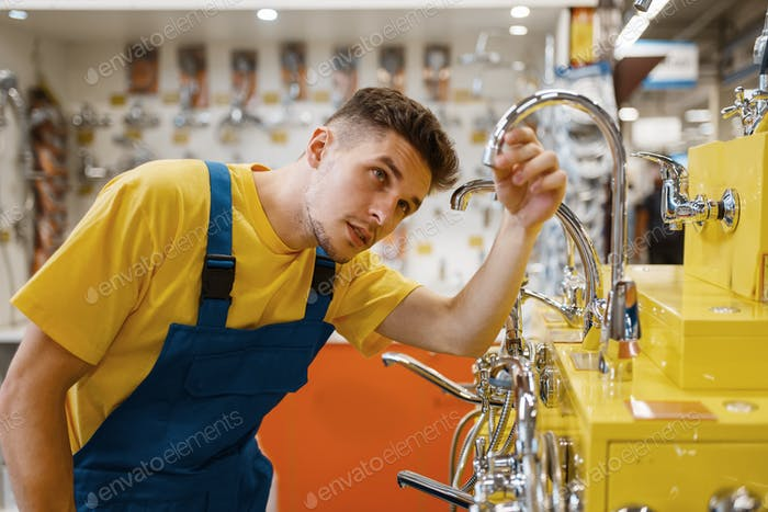 Male builder choosing water tap in hardware store
