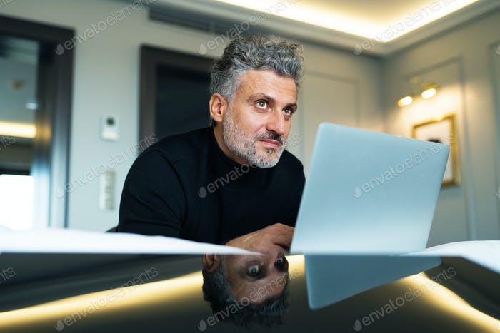 Thumbnail for Mature businessman with laptop in a hotel room.