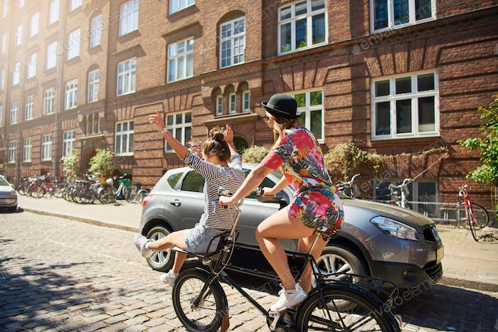Young women riding on a bicycle waving