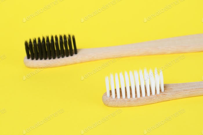 Natural bamboo toothbrushes on yellow background