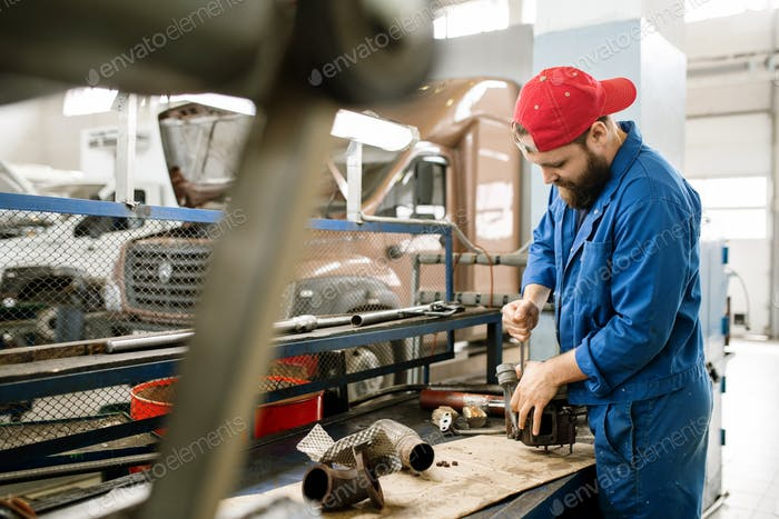 Young bearded repairman in workwear repairing part of car engine