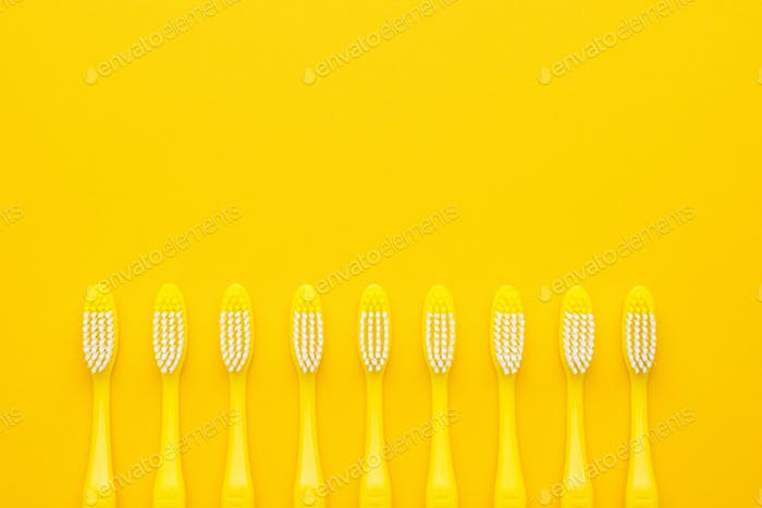 Plastic Toothbrushes On Yellow Background