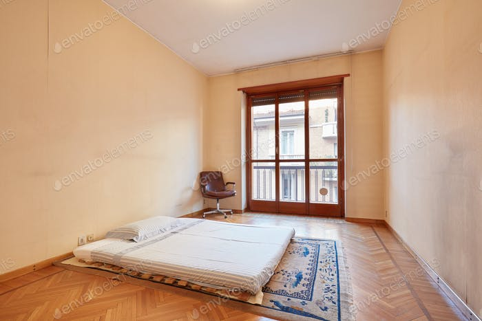 Bedroom with tatami bed and armchair in old apartment