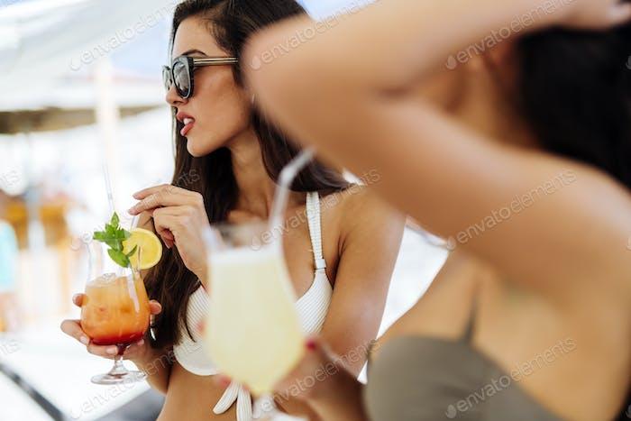 Glamouröse Mädchen trinken Getränke am Strand
