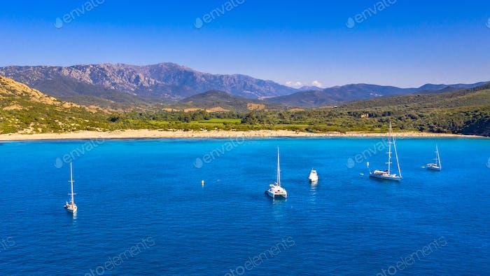 Sailboats moored in natural bay