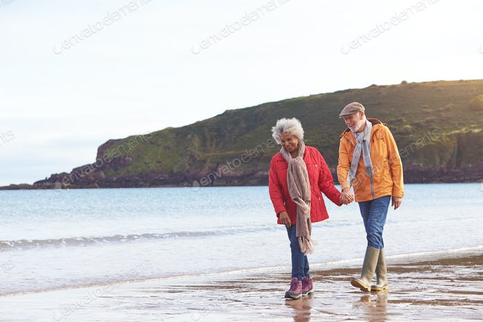 Senior Couple Hold Hands As They Walk Along Shoreline On Winter Beach Vacation