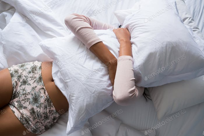 Woman holding pillow on bed