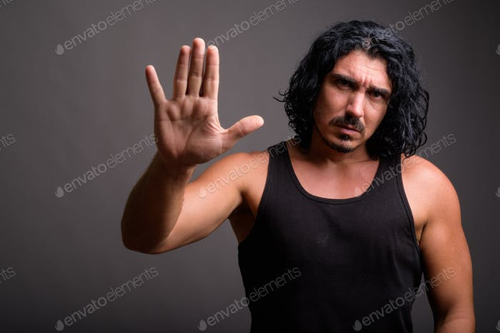 Handsome macho man with mustache against gray background