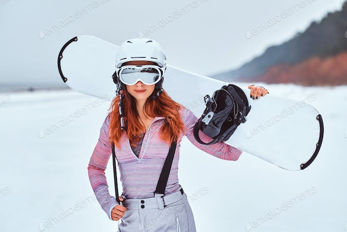 Beautiful redhead girl in protective helmet and goggles holding a snowboard on a snowy beach