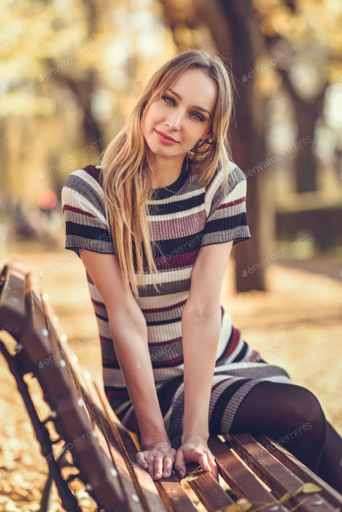 Young blonde woman sitting on a bench of a park