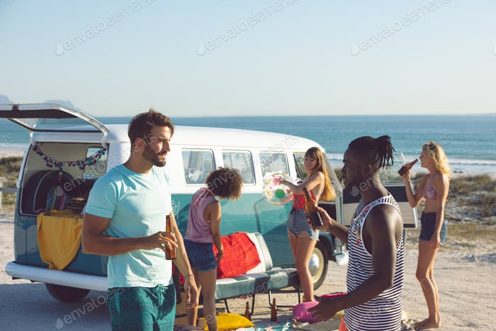 Side view of young group of diverse friends having fun near camper van at beach