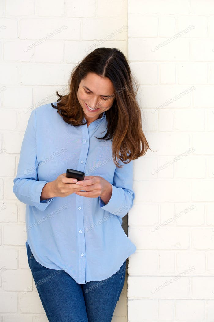 attractive woman leaning against wall and looking at cellphone