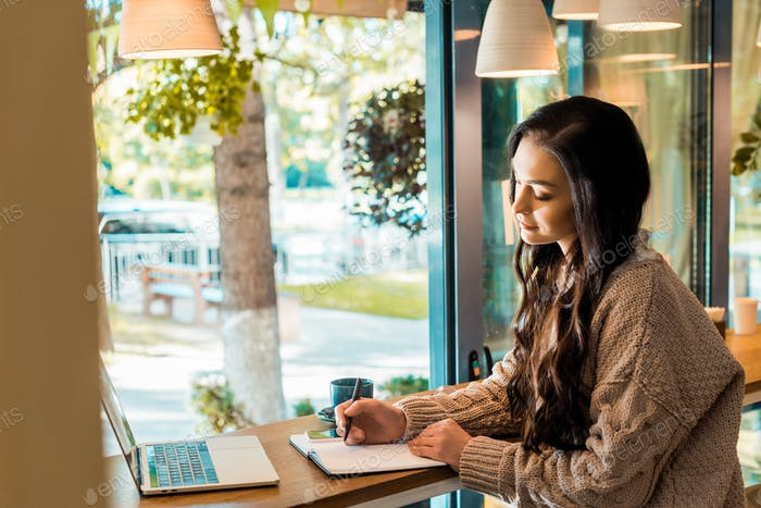 beautiful freelancer working with planner and laptop in coffee shop