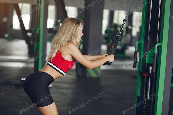 Sports blonde in a sportswear training in a gym