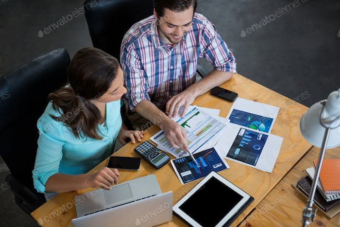 Business executives discussing charts and graphs on desk