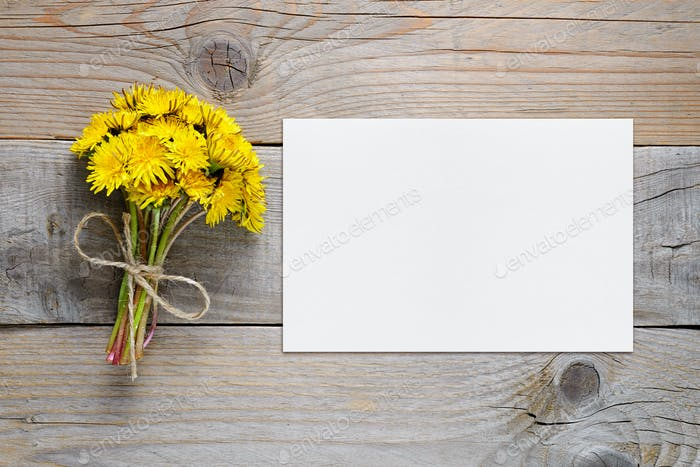 Bouquet of dandelion flowers and blank card on wooden background