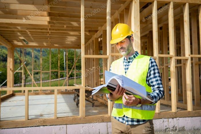Ingenieur mit Hardhat und Baupläne auf der Baustelle des Holzrahmenhauses im Bau