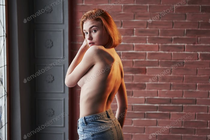Hot young blonde with bare chest and jeans stands against the brick wall