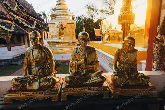 golden religious statues in ancient temple at Chiang Mai, Thailand