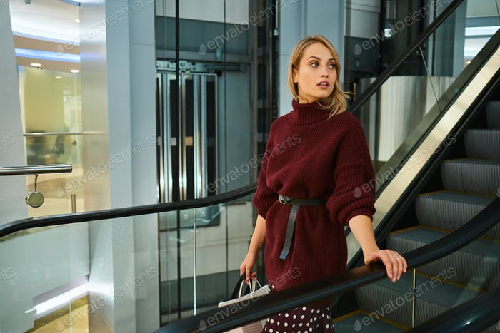 Beautiful stylish blond girl in sweater with shopping bags on escalator in shopping mall