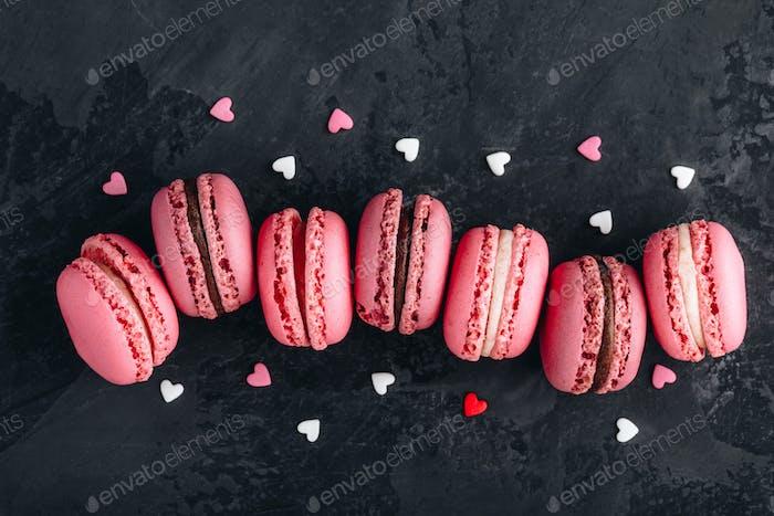 Valentinstag rosa Kuchen Macarons auf dunklem Hintergrund