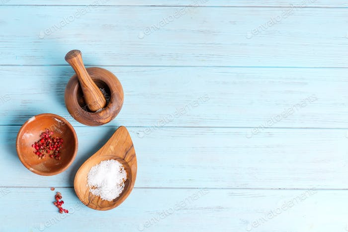 Top view set from wooden bowls with natural salt and condiments on a light blue wooden background