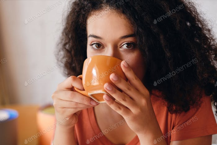 Portrait of young attractive woman with dark curly hair drinking coffee dreamily looking in camera